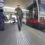 A blind man is walking on a tram platform using the tactile orientation system